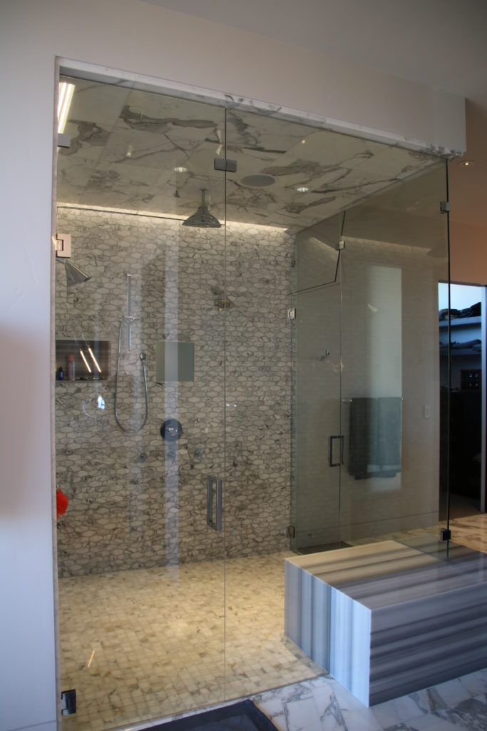 large frameless shower enclosure with 2 entry doors and transoms